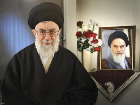Iran's Supreme Leader Ayatollah Ali Khamenei sits next to a portrait of late leader Ayatollah Ruhollah Khomeini in Tehran