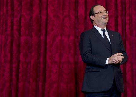 "France's President Hollande reacts during a ceremony where he named French singer and actress Renaud ""Grand Officier de la Legion d'Honneur"" at the Elysee Palace in Paris"