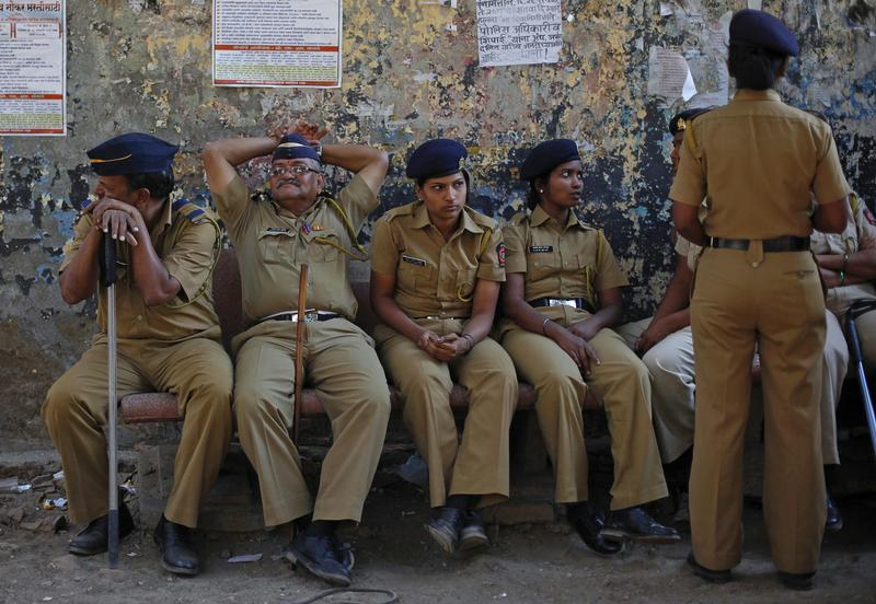 Policemen keep watch during a protest rally organised by various trade unions in Mumbai