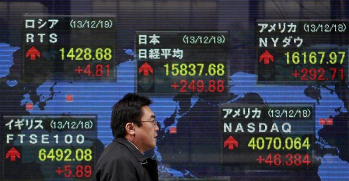 A pedestrian walks past an electronic board displaying various countries' share prices outside a brokerage in Tokyo