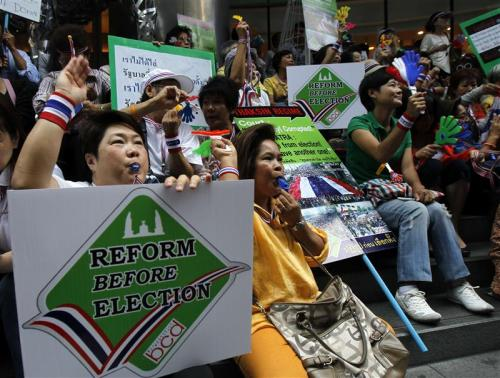 Anti-government protesters blow whistles and hold placards during a rally at Silom road in central Bangkok