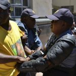 Police officer detains an African National Congress supporter after they tried to confront members of the opposition Democratic Alliance party as they marched in central Johannesburg