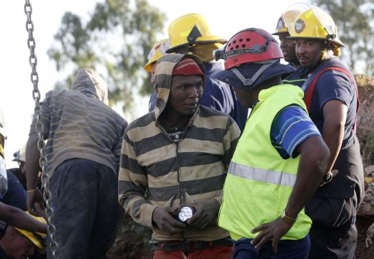 A suspected illegal miner talks to officials after being rescued from an abandoned gold shaft in Benoni