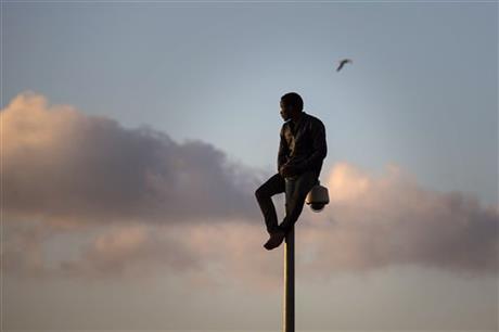 A sub-Saharan migrant sits on top of a pole