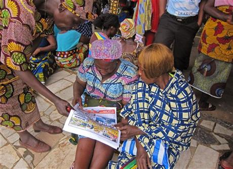 Woman read a newspaper as they protest outside the Liberian legislature in Monrovia