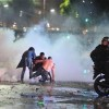 Soccer fans try to escape from a tear gas cloud and a police water cannon