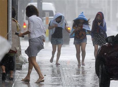 Women walk amid strong winds on a street in Naha, Okinawa