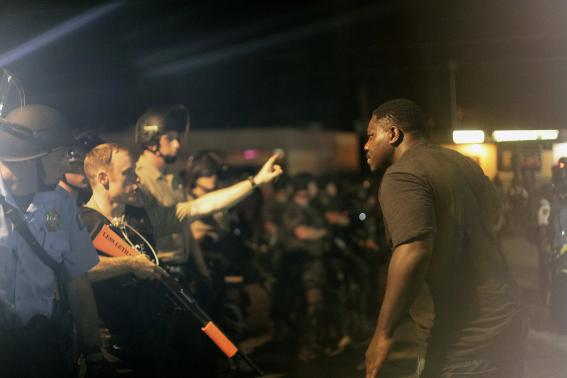 A demonstrator protesting against the shooting of Michael Brown talks to the police in Ferguson, Missouri