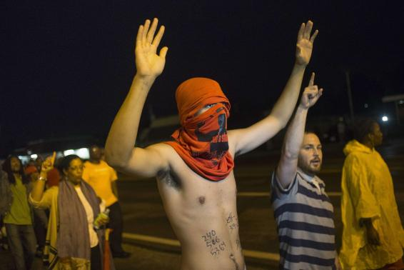 """Demonstrators shout """"Hands up, don't shoot,"""" while protesting the killing of unarmed black teen Michael Brown in Ferguson, Missouri"""