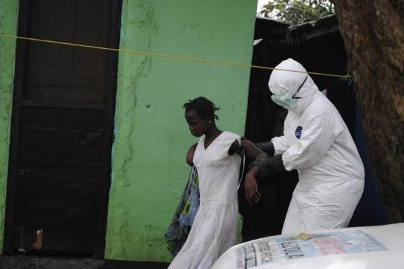 Health worker brings a woman suspected of having contracted the Ebola virus to an ambulance in Monrovia