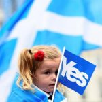 A young girl holds a flag at a 'Yes' campaign rally in Glasgow