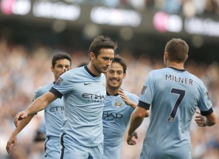 Manchester City's players run towards Frank Lampard after he scored a goal against Chelsea during their English Premier League soccer match at the Etihad stadium in Manchester