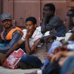 Rescued migrants sit on the ground at the Armed Forces of Malta Maritime Squadron base at Haywharf in Valletta's Marsamxett Harbour