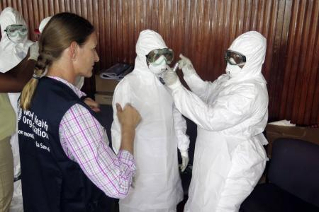 World Health Organization health worker teaches trainee health workers how to put on a protective suit in Freetown
