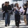 Injured Kurdish protester is carried by his friend as they clash with riot police in Diyarbakir