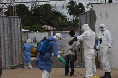 Health workers wearing protective equipment are disinfected outside the Island Clinic in Monrovia, where patients are treated for Ebola