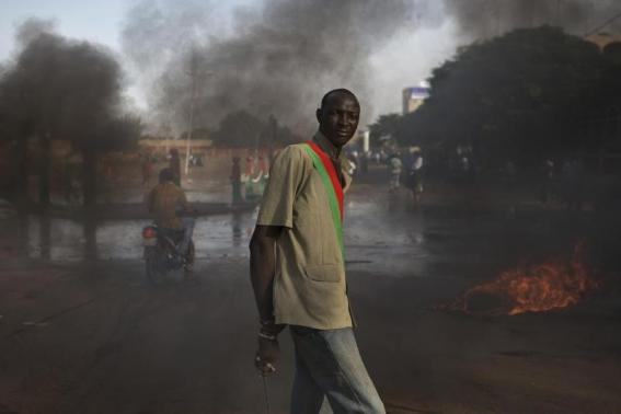 An anti-government protester wears a sash taken from the looted parliament building in Ouagadougou