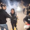 Protesters retreat while police officers deploy teargas to disperse a crowd comprised largely of student protesters during a protest against police violence in the U.S., in Berkeley