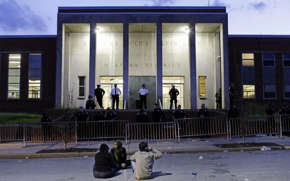 Protesters sit outside the Baltimore Police Department