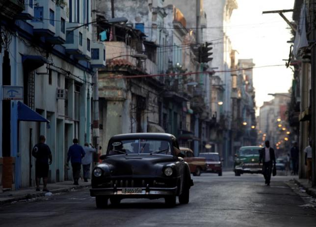 A car used as a taxi drives through the streets of Havana