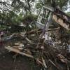 Amy Gilmour a volunteer from San Antonio Texas walks past a pile of debris which included parts of destroyed homes that amassed when the Blanco River flooded during the Memorial Day weekend rains in Wimberley Texas