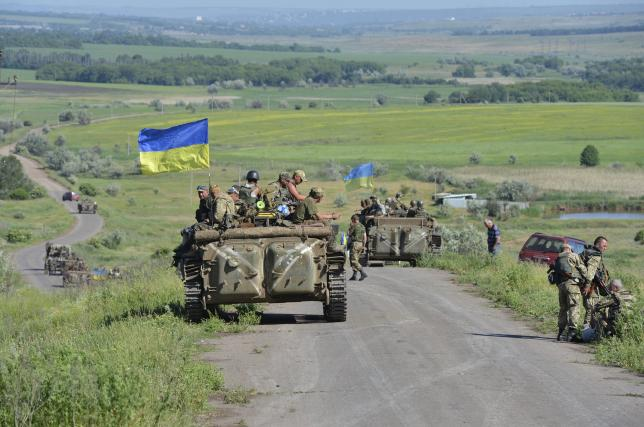 Members of the Ukrainian armed forces gather on the roadside near the village of Vidrodzhennya