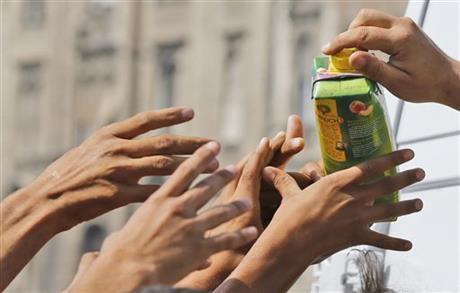 Migrants receive a juice donation