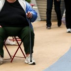 An overweight woman sits on a chair in Times Square in New York