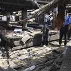 police officers inspect the site of a suicide bomb attack at a cattle market