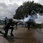 A riot policeman lobs a teargas canister to disperse supporters of the CORD during a protest at the premises hosting the headquarters of IEBC to demand the disbandment of the electoral body ahead of next year's election in Nairobi