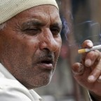 A man smokes a cigarette as he sits on a pavement along a road in Srinagar
