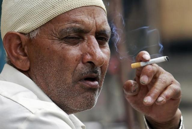 A man smokes a cigarette as he sits on a pavement along a road in Srinagar