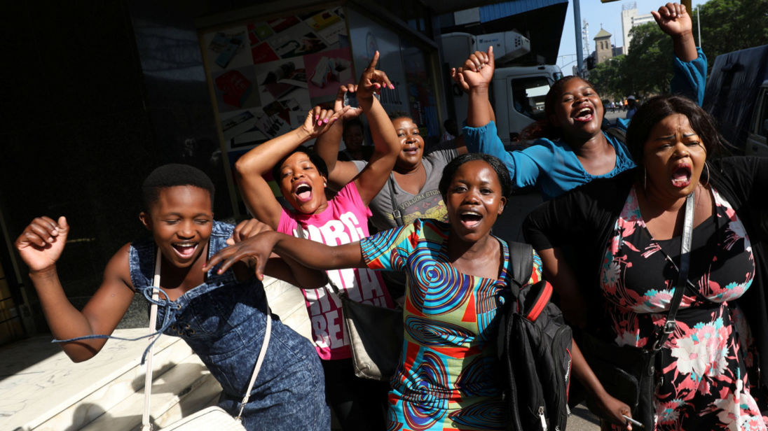 Zimbabweans celebrate in the morning sun after President Mugabe resigned in Harare